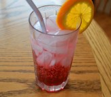 a glass with ice and red, juce cocktail with straw and an orange slice
