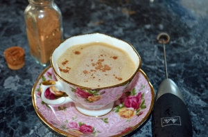 Creamy coffee in a floral teacup and saucer